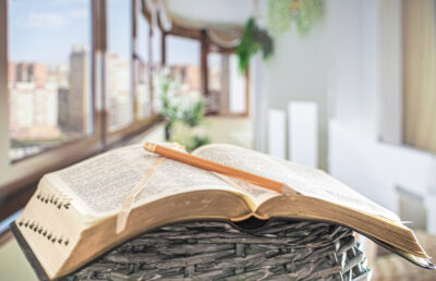Book Bible with pencil close-up, on the background of a beautiful terrace. Morning time.